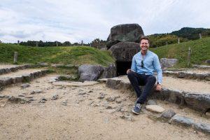 IshPerson sitzend vor ishibutai Kofun Steinstruktur