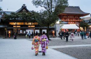 Frauen laufen durch Schrein bei Dämmerung in Japan
