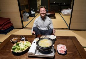 Japanisches Hot Pot Gericht Nabemono mit Person im Hintergrund