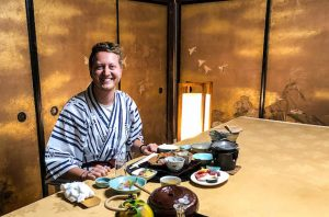 Person am Tisch mit Speisen im Ryokan