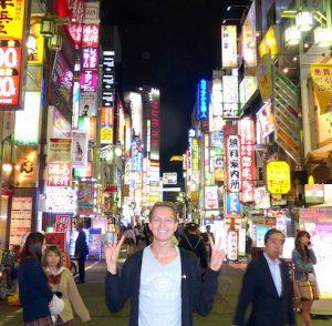 Belebte Straße mit Lichtern bei Nacht und Person davor
