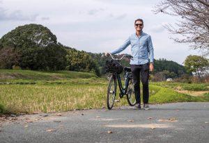 Person mit Fahrrad auf Weg mit Reisfeld daneben