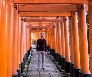 Japan Reisetipps zum Fushini Schrein mit orangenen Torii Bögen und Person