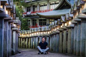 Laternen in Tempel mit Person sitzend davor