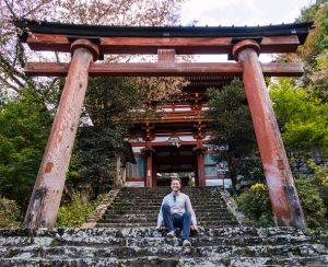 Torii Bogen und Eingang von Tempel in Yoshino mit Person sitzend auf den Stufen