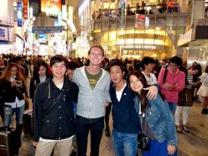 Gruppe von Personen in belebter japanischen Stadt bei Nacht