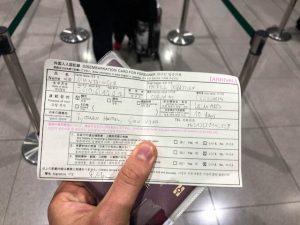 Einreiseformular für Japan in Hand gehalten