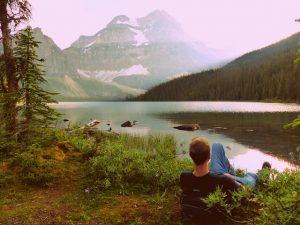 Backpacker liegt am See in Kanada mit Berg im Hintergrund