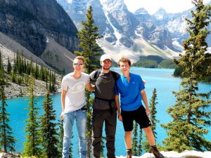 Drei Personen vor See im Nationalpark in den Rocky Mountains