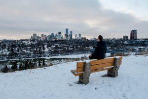 Person auf Bank mit Blick auf Skyline von Edmonton