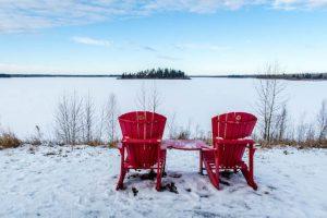 Rote Stühle vor Schnee und See