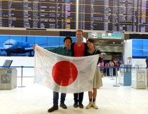Drei Personen mit Japan Flagge am Flughafen in Tokio