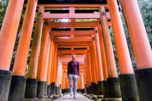 Orangene Torii Tore in japan mit Person in der Mitte