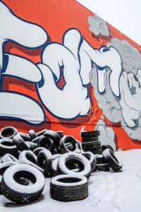 Reifen und bemalte Wand im Schnee