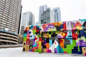 Bunt bemalte Wand mit Hochhäusern dahinter