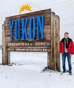 Yukon Straßenschild mit Person daneben im Schnee