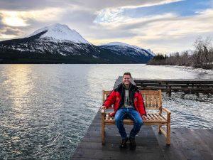 Person sitzt auf Bank am See mit Berg im Hintergrund