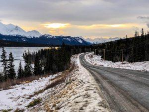 Straße mit See bei Sonnenuntergang