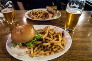 Burger Pommes Bier auf Tisch