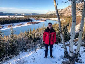 Person vor Aussicht auf Fluss und Wälder im Yukon