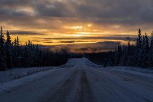 Sonnenaufgang auf verschneiter Straße