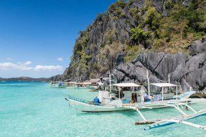 Wunderschöner Strand mit Felsen und Boot in Coron