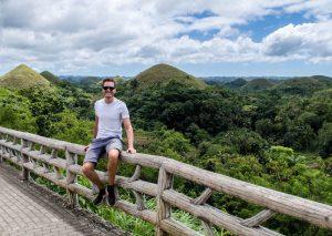 Ich sitze vor den chocolate Hills auf Bohol in den Philippinen