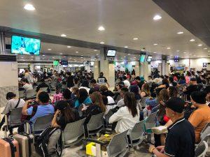 Viele Menschen am Flughafen auf Bänken