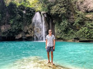 Person vor blauem Wasserfall südlich von Moalboal Cebu