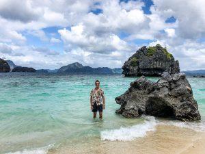 Person im Meer neben Felsen