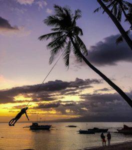 Sonnenuntergang mit Palme und Person an Seil am Strand