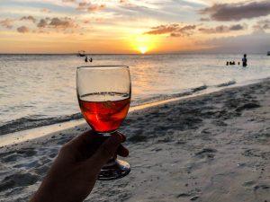 Glas mit Rum am Strand vor Sonnenuntergang
