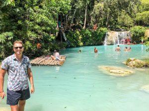 Person vor Wasserfall im Regenwald