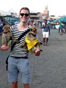 Person mit zwei Affen auf dem Marktplatz in Marrakesch